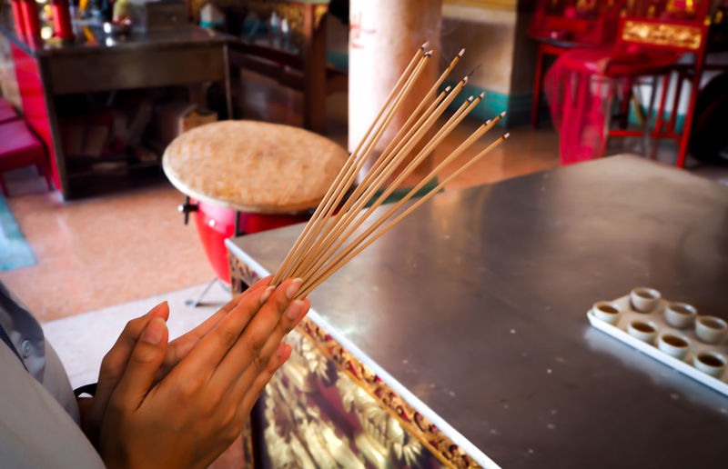 Cropped Hands Holding Incense Sticks While Praying In Temple