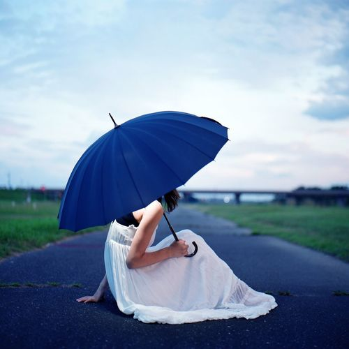 Side View Of Woman With Umbrella Sitting On Road