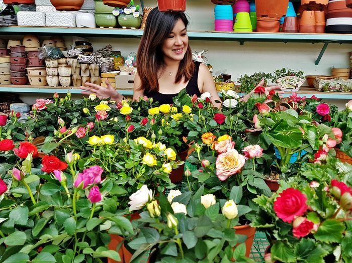 Young woman standing by flowering plants at market stall