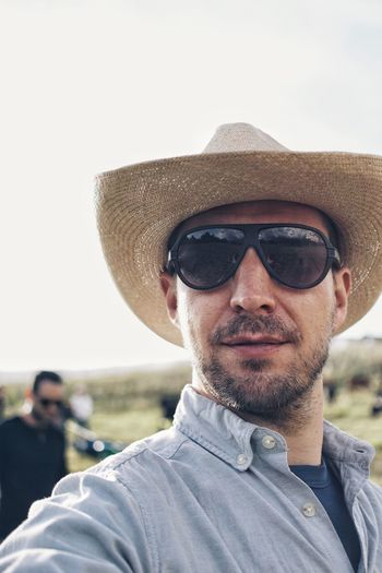 Portrait Of Mid Adult Man Wearing Sunglasses And Straw Hat While Standing At Field