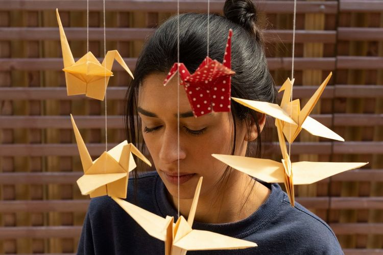 Woman standing by paper origami