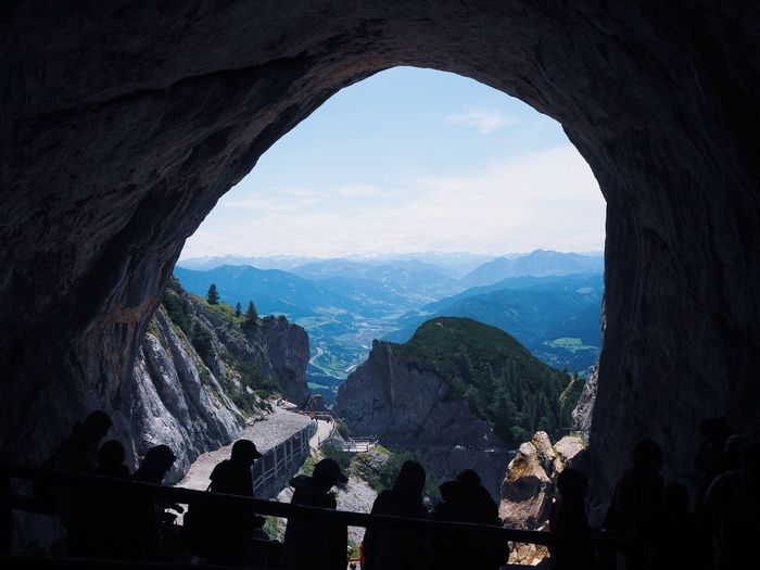 People seen through arch against mountains