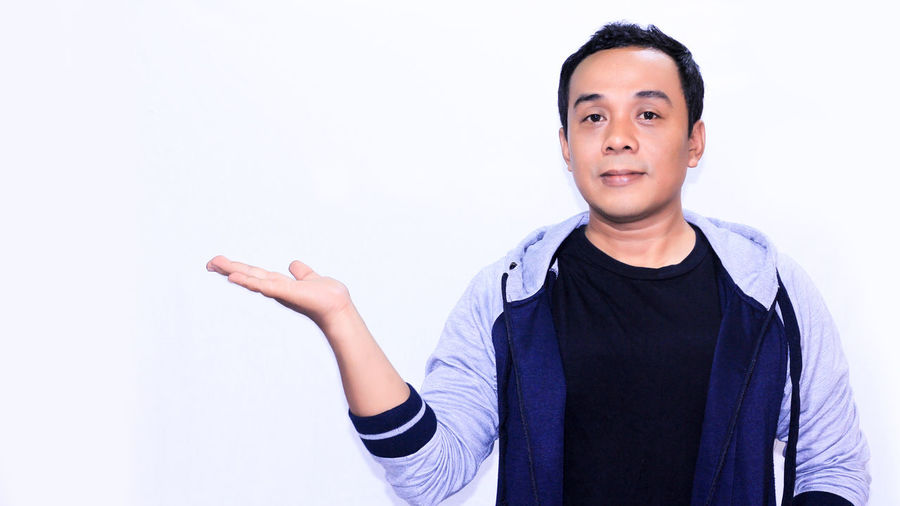 Portrait smile asian man with his gesture Looking At Camera Portrait Studio Shot Front View White Background One Person Casual Clothing Indoors  Gesturing Smiling Waist Up Lifestyles Standing Young Adult Young Men Men Cut Out Clothing