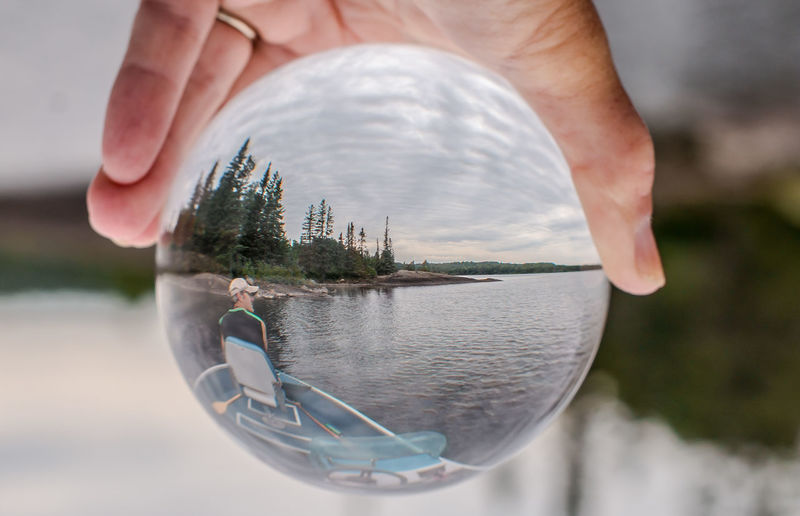Close-up of hand holding crystal ball with reflection in water