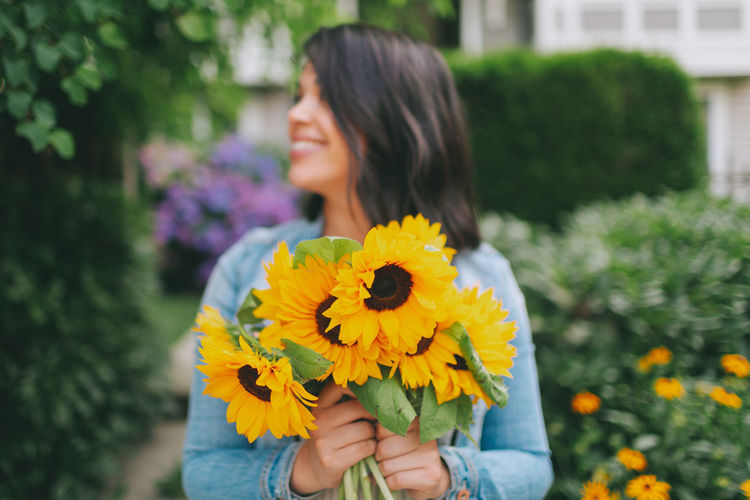 A woman holding a bouquet of sunflowers. Beautiful Woman Woman Holding Bouquet Sunflowers Smiling Happy Flowers