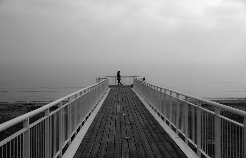 Woman standing on jetty by sea against sky