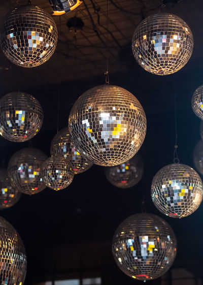 Low angle view of illuminated disco balls hanging from ceiling