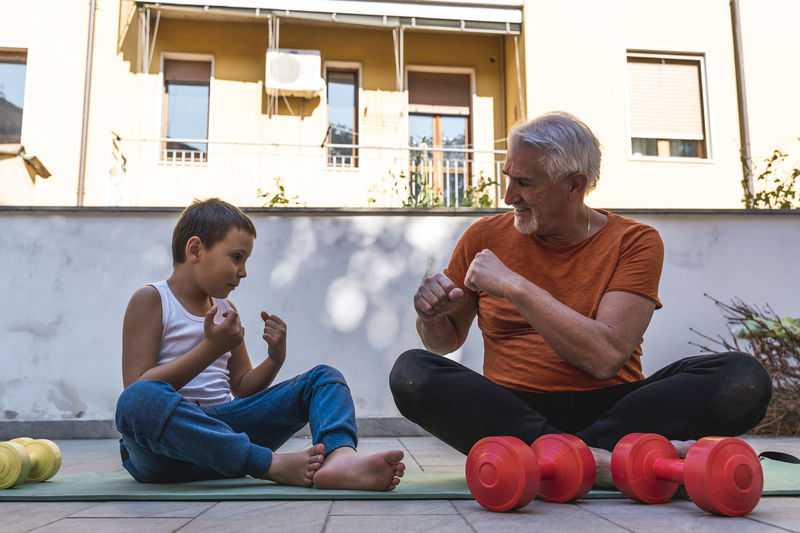 Grandfather and grandson training on terrace