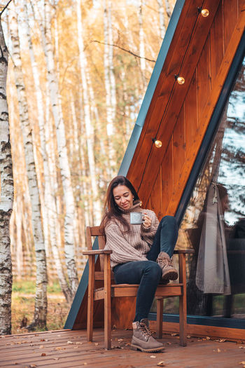 Portrait of young woman sitting on chair outdoors