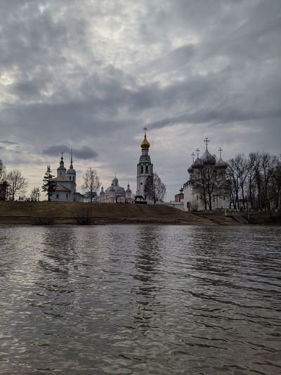 View of river by buildings against cloudy sky
