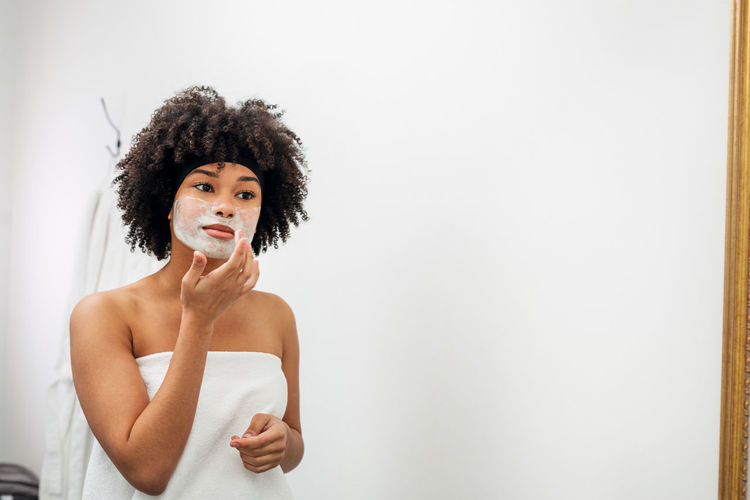 One Person Indoors  Copy Space Lifestyles Portrait Hairstyle Standing Curly Hair Young Women Front View Mirror Applying Cream Natural Mask Looking Reflection Beautiful Woman Wrapped White Towel