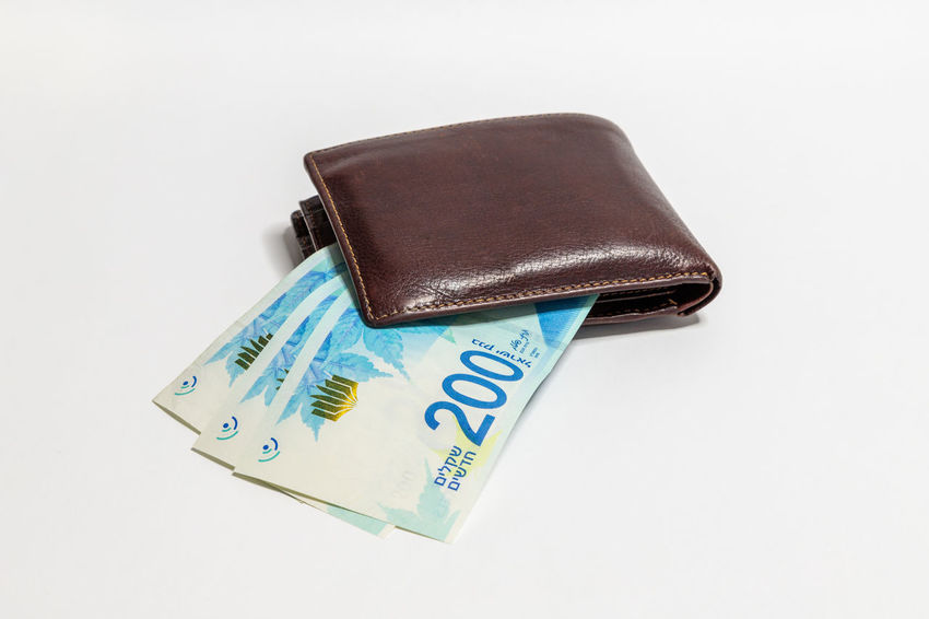 A brown leather purse and three hundred shekel banknotes sticking out of it isolated on a white background Business Economy Leather New Rich Shopping Bank Banknote Cash Close-up Commerce Finance Investment Israel Money Paper Currency Pay Purse Savings Shekel Sheqel New Studio Shot Symbol Wealth White Background