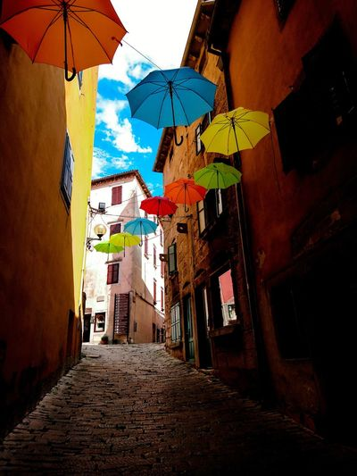 Flying umbrellas Flying Umbrellas Flying Sunshine EyeEmNewHere EyeEm Best Shots Urban Urbanphotography Sunlight Lane Alley Multi Colored Architecture Built Structure Umbrella