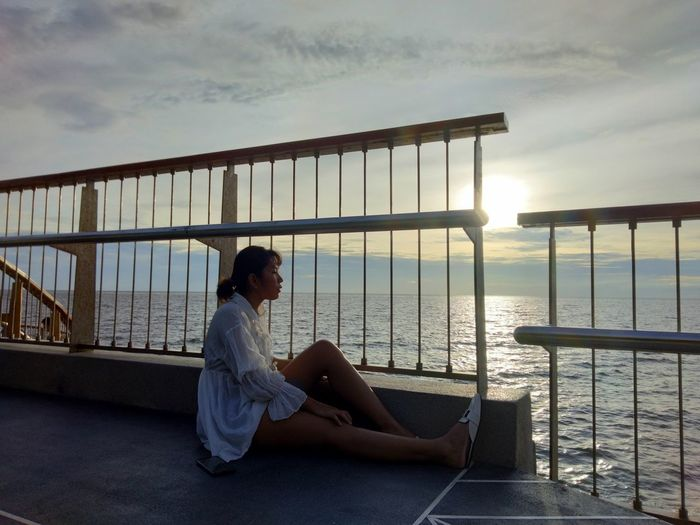 Woman sitting on railing against sky during sunset
