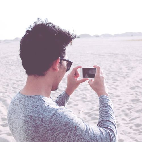 Man photographing from mobile phone at sandy beach