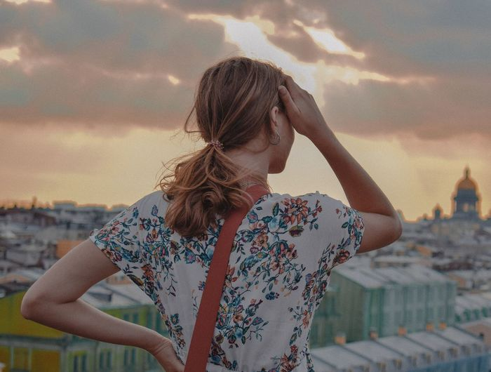 Senior woman standing by cityscape against sky during sunset