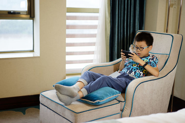 Child Sitting One Person Furniture Technology Indoors  Living Room Sofa Childhood Domestic Room Full Length Relaxation Wireless Technology Holding Communication Leisure Activity Connection Offspring Side View Lifestyles Digital Native