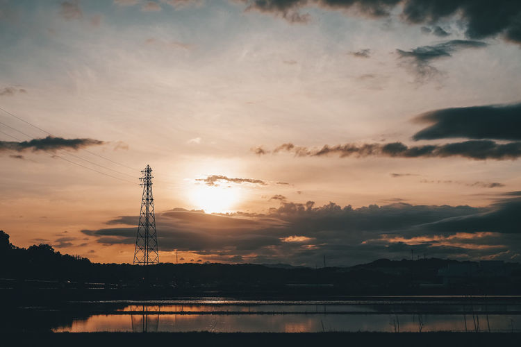 Silhouette electricity pylon by lake against sky during sunset