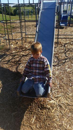Boy kneeling on slide at playground