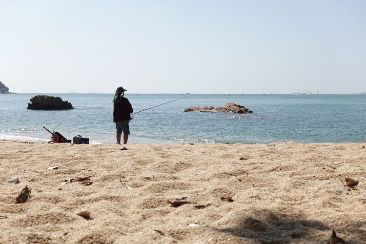 Rear view of man fishing on beach against clear sky