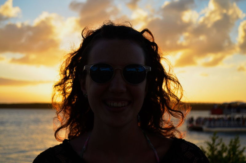 Close-Up Of Smiling Young Woman Wearing Sunglasses At Sea Against Sky During Sunset