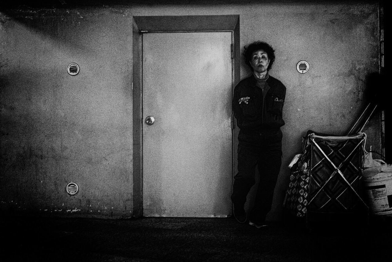 portrait, looking at camera, one person, full length, real people, standing, architecture, security, adult, front view, protection, indoors, safety, building, lifestyles, casual clothing, entrance, wall - building feature, door, uniform