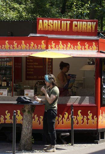 Currywurst!!! Berlin Streetfood Casual Clothing Communication Currywurst Currywurst!!! Day Full Length Imbissstand Men One Person Outdoors Real People Standing Text Tourism Young Adult