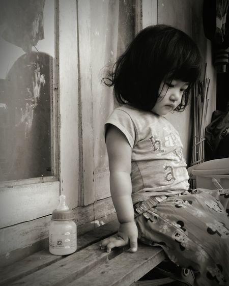 Cute girl sitting by window