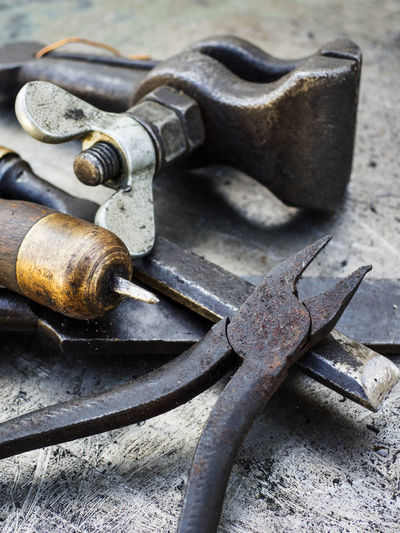 Close-up of various rusty tools on metal table