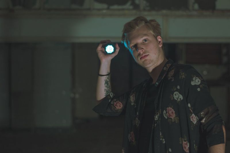 Portrait of man holding flashlight at night