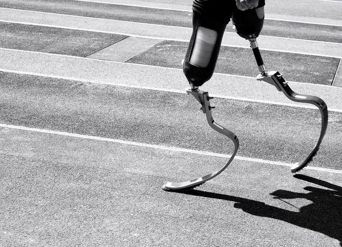 Low section of person with prosthetic leg on street