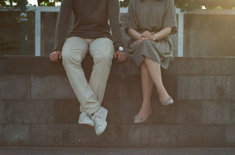 Low section of couple sitting on railing