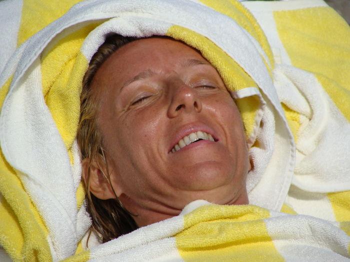 Close-up of smiling mature woman sunbathing