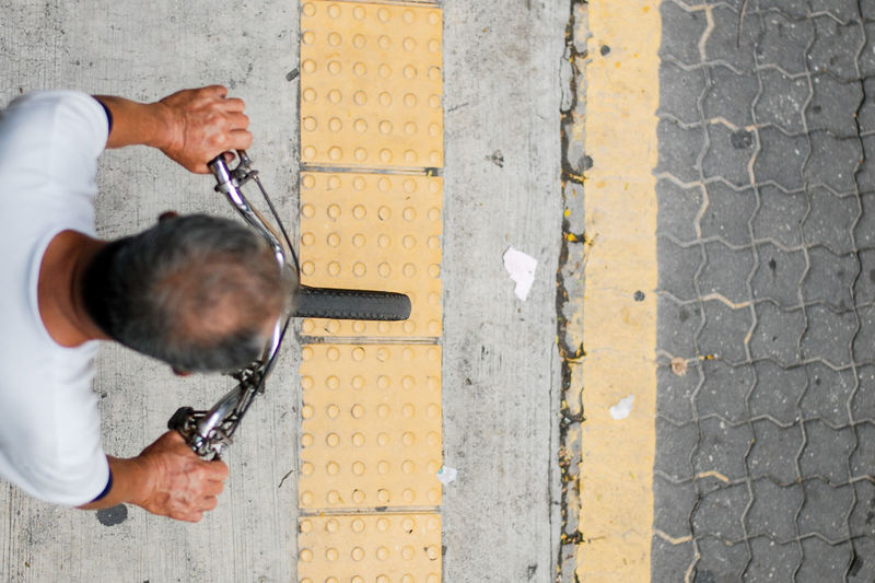 Directly above shot of man riding bicycle on footpath