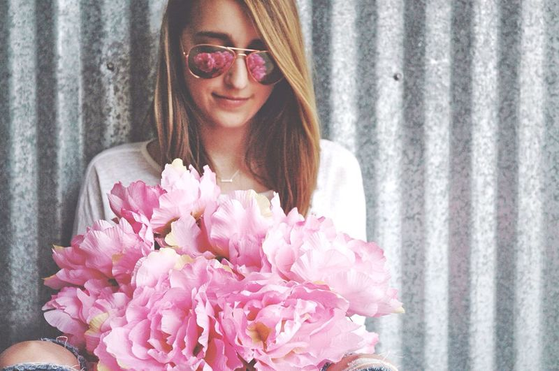 Portrait of smiling young woman standing by pink flowers