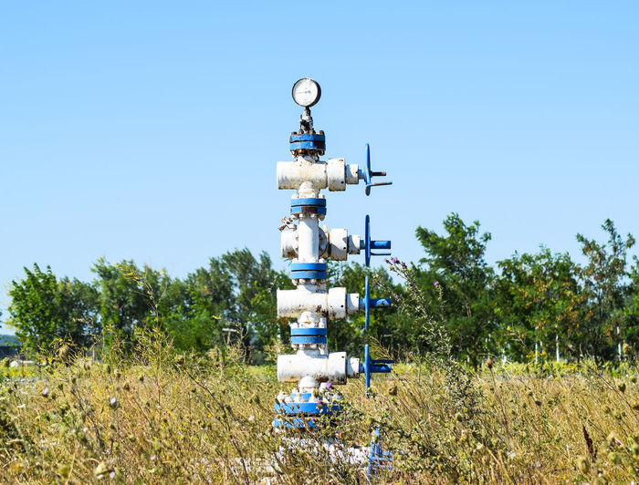 Blue oil pump on grassy field against clear blue sky