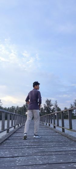 Rear view of man standing on footpath against sky