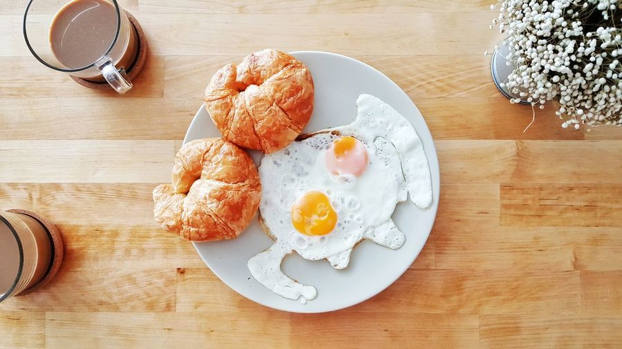 Breakfast set of croissants and fried eggs. Croissant Fried Eggs Breakfast Eggs Food Food And Drink Table Wooden Top View Coffee