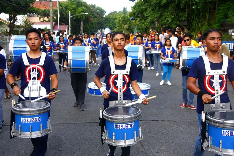 members of a marching band play music during a parade ASIA Asian  Philippines Filipino People Human Music Musician Drum Drummer Musical Instrument Drum - Percussion Instrument Parade Marching Band Festival Antipolo, Rizal Ph Sumakah Festival Fiesta Crowd Arts Culture And Entertainment Brass Instrument  Percussion Instrument Drum Kit Drumstick Musical Equipment Marching