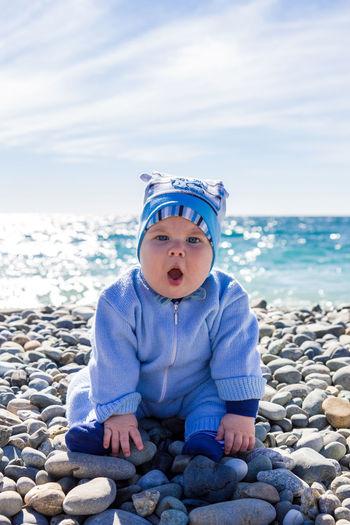 Boy sitting on rock at beach against sky