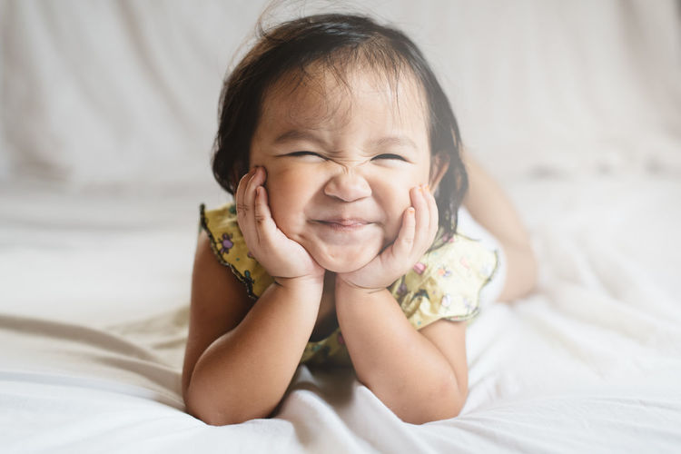 Portrait of cute baby girl lying on bed at home