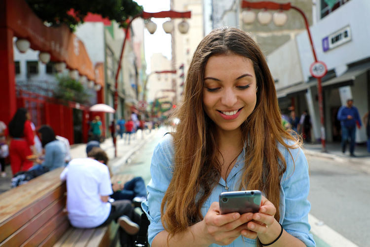 Smiling young woman using mobile phone against buildings in city