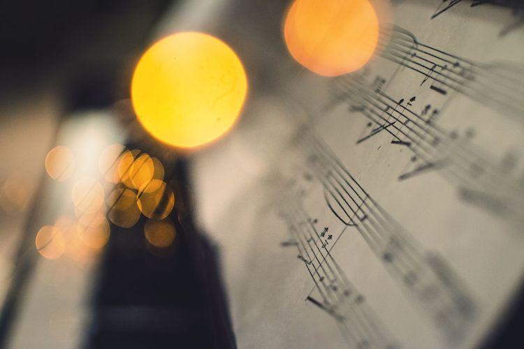 Close-up of illuminated lighting equipment and sheet music