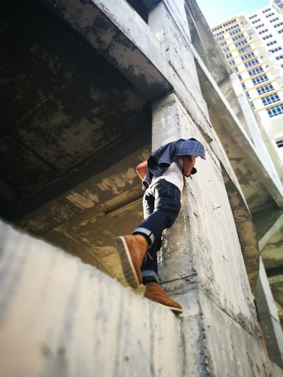 Low Angle View Of Man On Retaining Wall In Under Construction Building