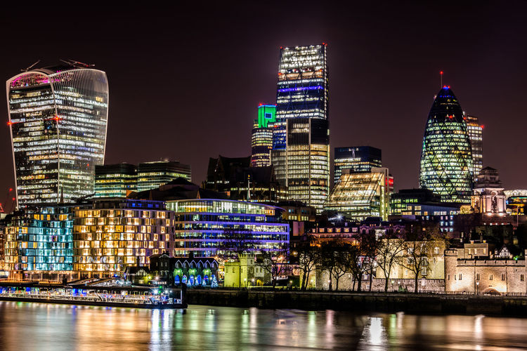 Thames river against illuminated buildings at night