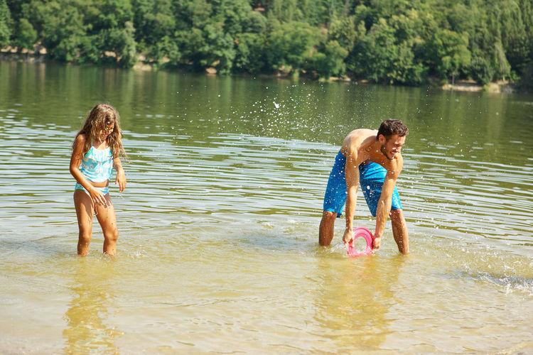 Shirtless Man With Daughter Splashing Water In Lake
