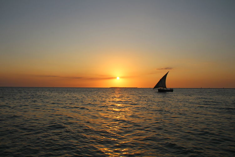Silhouette Sailboat Sailing On Sea Against Clear Sky During Sunset