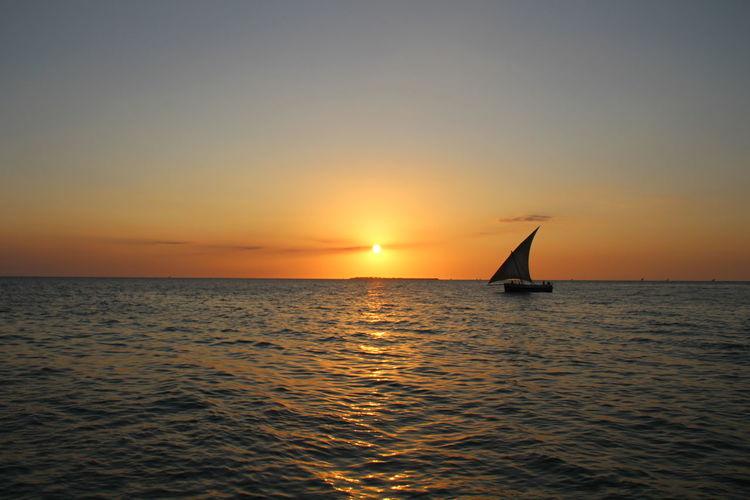 EyeEm Selects Zanzibar Africa Sunset Sea Horizon Over Water Sailboat Sailing Sun Water Scenics Nautical Vessel Sky Nature Tranquil Scene Horizon Dramatic Sky Silhouette Reflection Sunlight Dusk Travel Cloud - Sky Summer Road Tripping