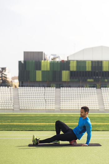 Side view of man sitting on grass against building
