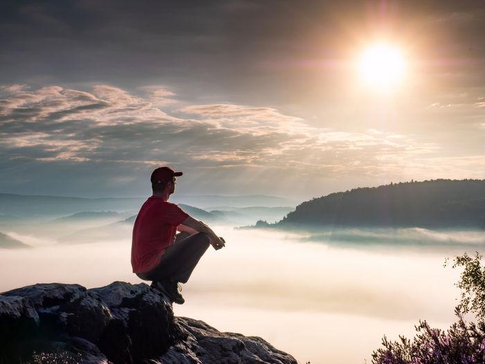 Blissful man squatting on rocks enjoying scenery of misty saxon park, enchantment with nature show